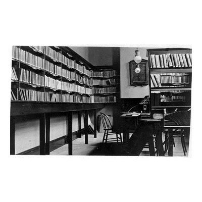 Picture postcard of interior of Lilydale Lending Library in Mechanics Institute building, Castella Street, Lilydale. Shows shelves of books, librarian's desk and honour roll on wall.