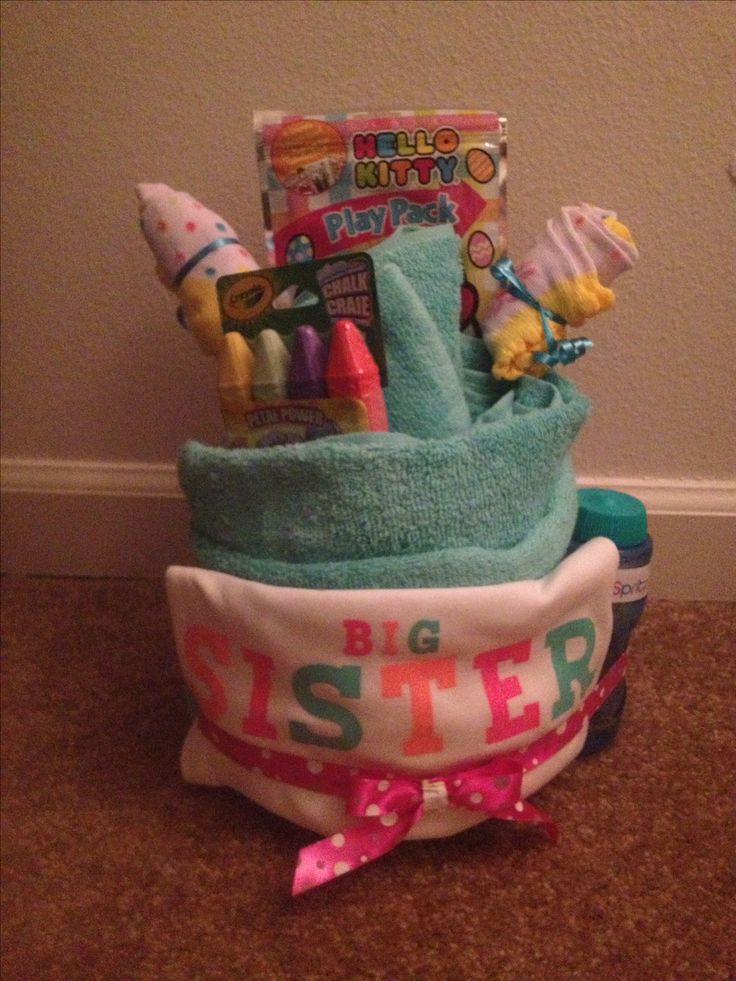 "A Big Sister ""Cake"" so the older sibling won't feel left out at the baby shower. I made this using a bath towel. I tied it off with some pretty ribbon and added some neat little prizes. I made two sock roses too. I bought the Big Sister shirt at Carter's. #bigsistercake #bigsister"
