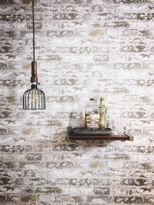 My first big makeover project! Faux exposed brick white wash wallpaper. Light from Antrohopogie, shelves, glass bottle and metal tray from Etsy. Glasses from Home Goods.