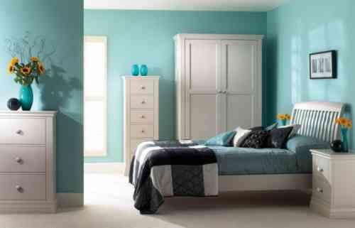 des murs turquoise et un mobilier blanc et élégant dans la chambre à coucher