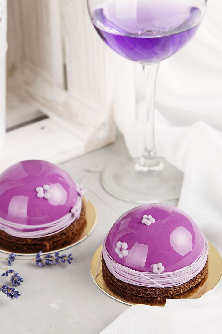 Romantic french pastries with pink mirror glaze cover on pastel background with wine glass and lavender flowers. Romantic holiday concept. Shallow focus