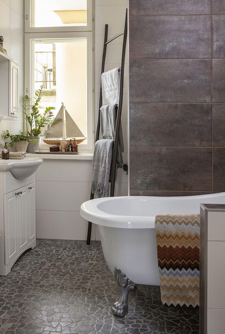Kauniisti remontoitu kylpyhuone sai jäädä ennalleen. Lattian luonnonkivilaatat, seinälaatat ja kiinteät kalusteet ovat Virosta.