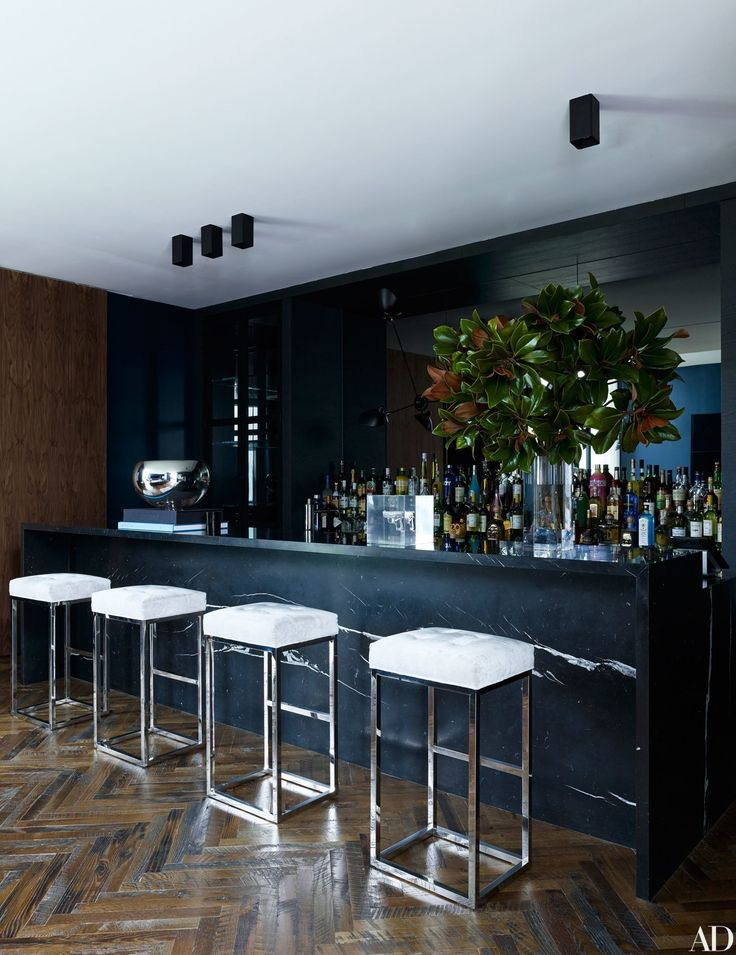 The bar's polished-marble top is contrasted with the reclaimed-wood flooring in a herringbone pattern | archdigest.com