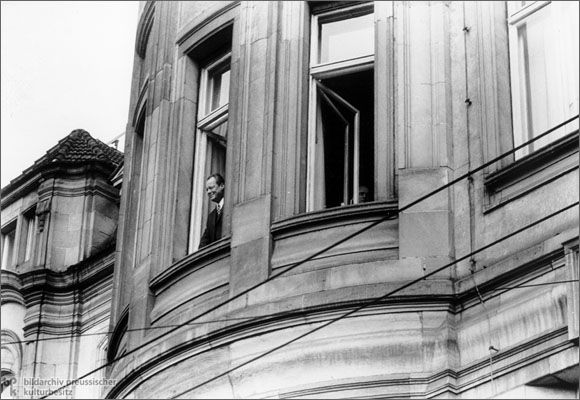 Willy Brandt at a Window in Erfurt (March 19, 1970)-To prepare treaties aimed at normalizing the relationship between the GDR and the Federal Republic, Chancellor Willy Brandt traveled to Erfurt (East Germany) in March of 1970 for his first meeting with Willi Stoph, the Chairman of the Council of Ministers of the GDR. To the great displeasure of the SED leadership, the local population gave Brandt a warm welcome. In this photograph, Brandt stands at an open third-floor window in the Hotel…