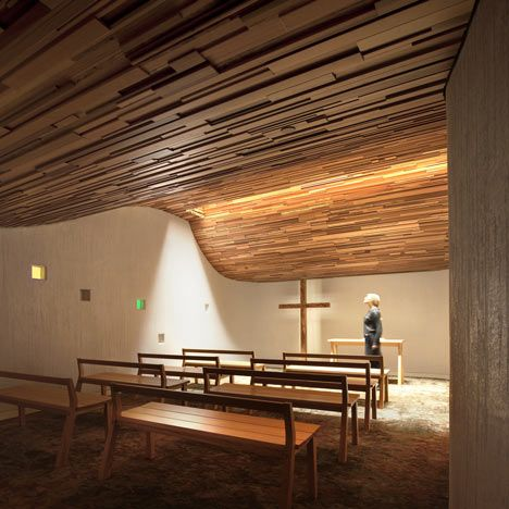 A wave-like wooden ceiling undulates above the heads of students atthis chapel