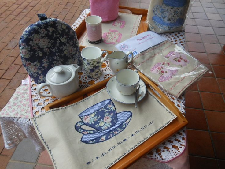 Tray cloths with appliqued tea cups and monogram wording.  Matching tea cozies and even a teapot for two.