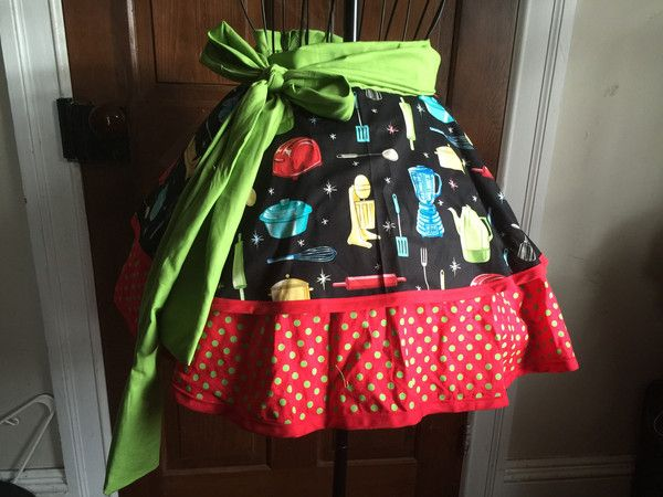 If you have a love of retro kitchens, you'll love this half apron. It features retro kitchen appliances on the skirt, red with green polka dots on the underskir
