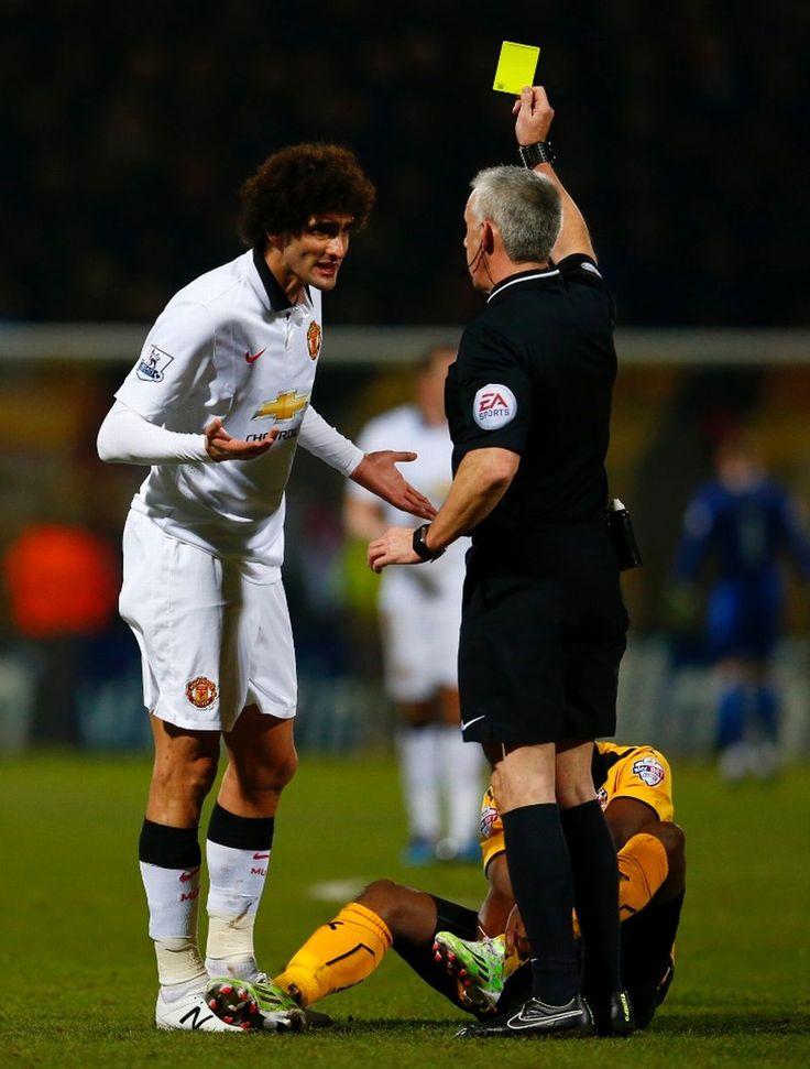 Marouane Fellaini argues with referee Chris Foy as he receives a yellow card