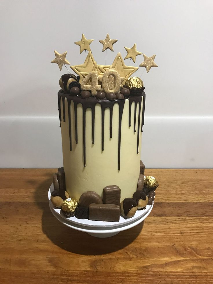 """This 10"""" tall cake with a smooth buttercream finish, chocolate drip, hand cut and painted decorations was covered with maltesers, tim tams, caramel crowns, ferrero roches and cake pops.    There were left overs and yes, I did eat them all."""