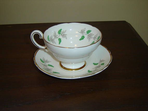 """Cup and saucer in a grape vine pattern, gold accenting  The cup is 2 1/2"""" (6.4 cm) high x 4"""" (10.2 cm) at the brim and the saucer is 5 9/16"""" (14.1 cm) in diameter  This set is in near mint condition and only appears to have seen use as a collectible  Made of fine bone china from England by Crown Staffordshire    These items have no nicks, chips, cracks, or signs of repair 