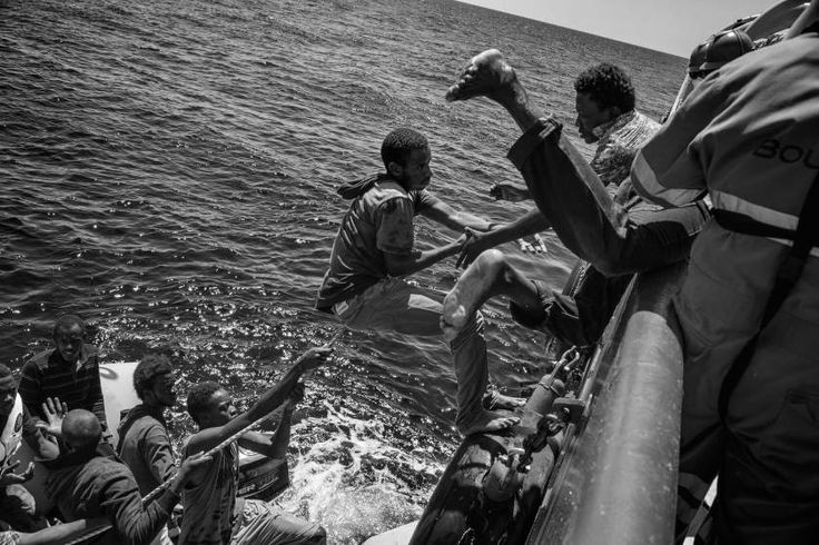 Contemporary Issues, 2nd prize stories. Migrants climb on board of a rescue ship by Doctors without Borders to escape their sinking rubber dinghy. Strait of Sicily, Mediterranean Sea, Aug. 21, 2015.