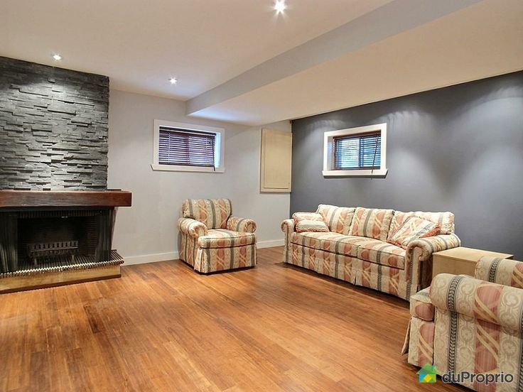 Bright basement family room with renovated bamboo floors and fireplace facade.