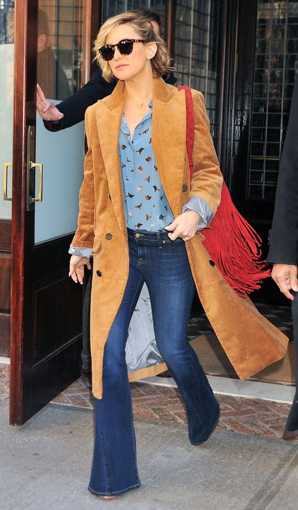 Kate Hudson in a printed blouse, flare jeans and brown suede long coat