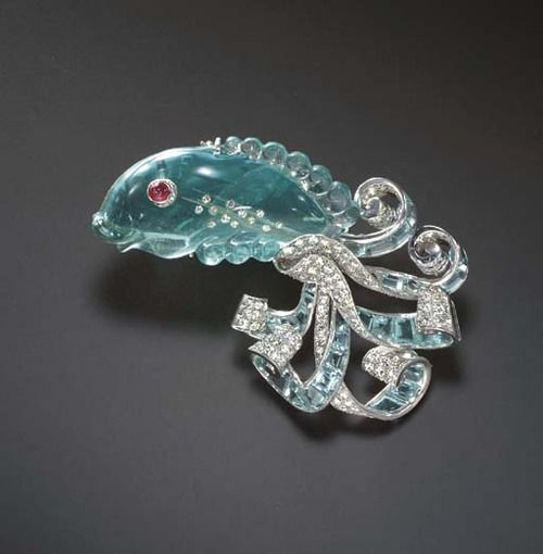 The carved aquamarine fish, with a cabochon ruby eye and single-cut diamond detail, extending a scrolling pavé-set diamond and calibré-cut aquamarine tail, mounted in platinum, (one aquamarine deficient), circa 1935. ~~~ (sold:  78,870.00)  ---- (Estimated value: 30,000 - 50,000.)