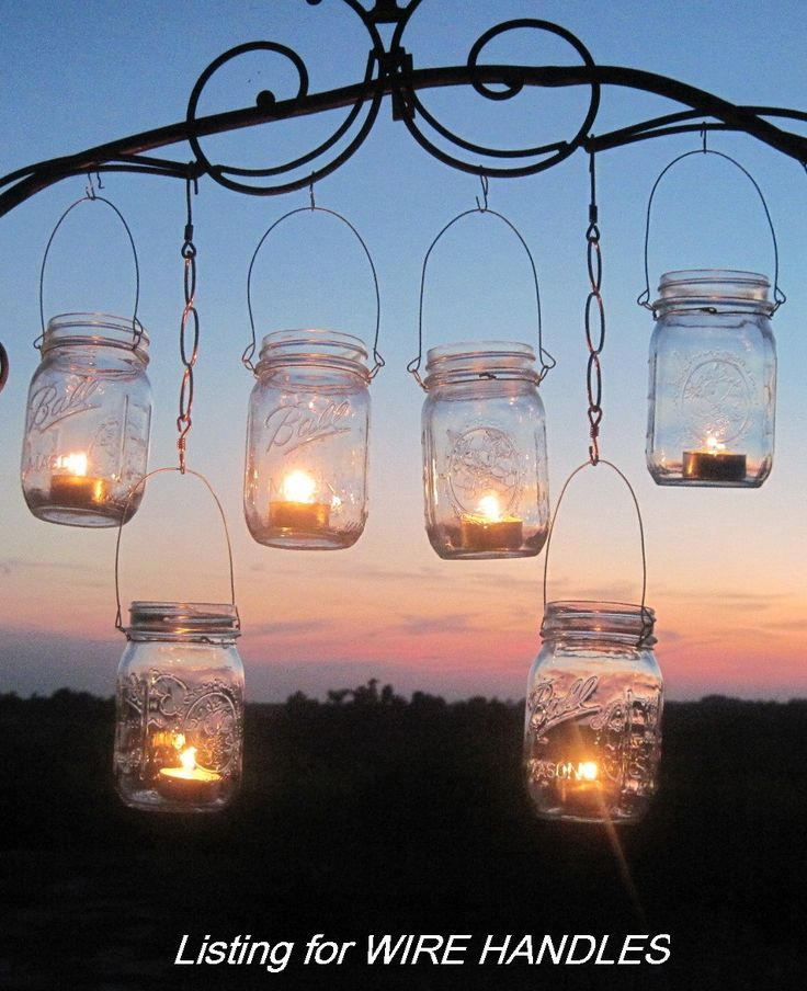 """Anyone can makes these out of Canning Jars and old wire coathangers.  OR you can buy them at Pottery Barn.  I like to make these and hang them from trees when entertaining outside.  I put a little sand or pebbles in the bottom of each jar to hold the candle in place.  You can also use colored glass marbles or sand with glitter added for a more """"sparkly"""" outdoor party :)"""