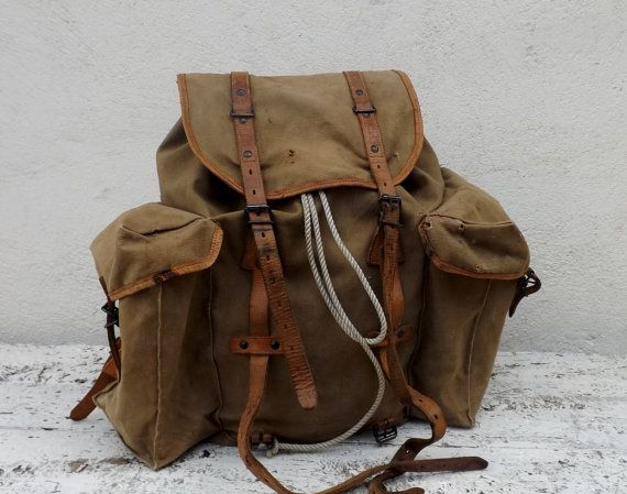 A vintage framed, canvas backpack probably French military and now very on-trend. The canvas is a mustard colour with tan leather fasteners and edgings throughout. The metal frame is flexible and adapts its shape when in use; the lower back strap is webbing and can be adjusted. The