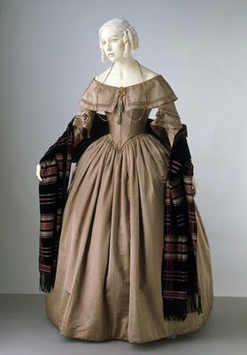 1840's dress. Note the turned down wide collar and shawl. The fuller skirt is also present and the pointed bodice. Silk, taffeta or heavy satin.