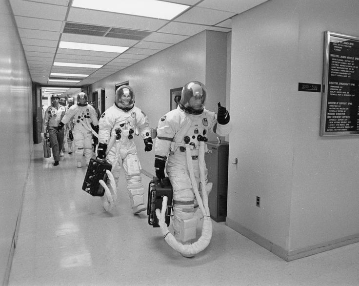 Apollo 16 John Young gives a 'thumb up' to well-wishers gathered in MSOB hallway as he, Ken Mattingly, and Charlie Duke leave to board the transfer van to the pad 16 April 1972.