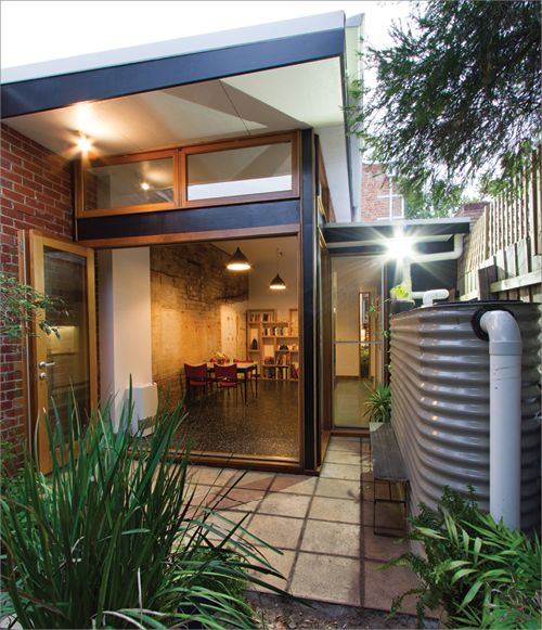 An energy efficient renovation viewed from the home's garden area, which includes a rainwater tank; the inside of the home can be seen in the background through large bi-fold doors.