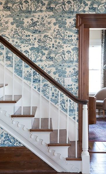 Swirling blue and white wallpaper give a breath of freshness contrasting against the original mouldings, flooring, and stairs in this historic Tennessee farmhouse as featured in Garden & Gun.
