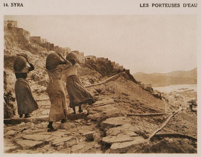 Άνω Σύρος. Γυναίκες που κουβαλούν νερό. Syra – Les porteuses d'eau. Χρονολογία έκδοσης:1919 BAUD-BOVY, Daniel, BOISSONNAS, Frédéric. Des Cyclades en Crète au gré du vent, Γενεύη, Boissonnas & Co, 1919.