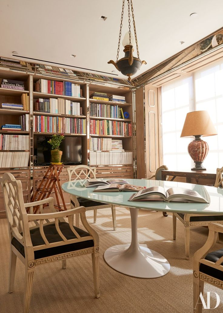 Strips of antiqued mirror on the moldings and bookcases add subtle sparkle to the conference room