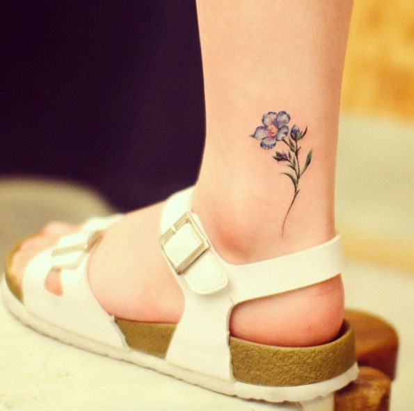 Flax flower ankle tattoo by Grain