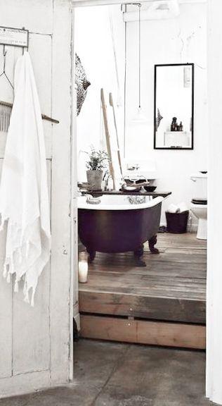 = black clawfoot bath, low hung pendants and rustic wood flooring