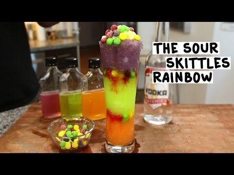 THE SOUR SKITTLES RAINBOW Orange Layer: 1 1/2 oz. (45ml) Orange Sour Skittles Infused Vodka 1/2 oz. (15ml) Sweet & Sour Mix 1 oz. (30ml) Orange Juice Green Layer: 1 1/2 oz. (45ml) Green Sour Skittles Infused Vodka 1/2 oz. (15ml) Sweet & Sour Mix 1 oz. (30ml) Lemon Lime Soda Purple Layer: 1 1/2 oz. (45ml) Purple Sour Skittles Infused Vodka 1/2 oz. (15ml) Sweet & Sour Mix 1 oz. (30ml) Purple Kool-Aid Top with Frozen Lemonade Garnish: Sour Skittl...
