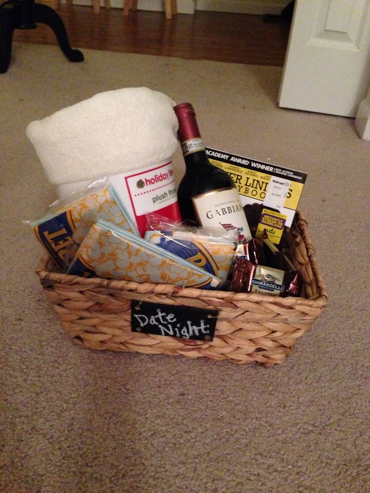 "Holiday Grab Bag Gift Idea: ""Date Night"" Includes a basket filled with a throw blanket, wine, DVD, popcorn, and dark chocolate."