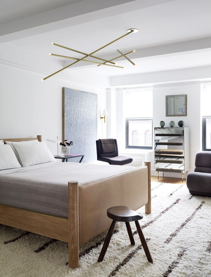 Neutral bedroom with black and white rug and Sputnik light fixture