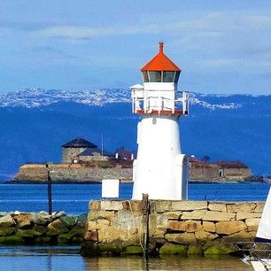 A small lighthouse and the island Munkholmen in Trondheim, Norway