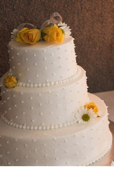 The cake was a three-layer chocolate cake with buttercream icing. It had swiss dots and beads around each layer. My cousin, Juli, who did the flowers for the wedding added white daisies and yellow roses to the cake.