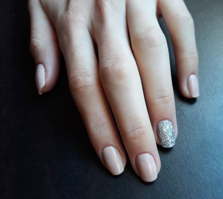 Simple nude colour nails with sparkle accent.
