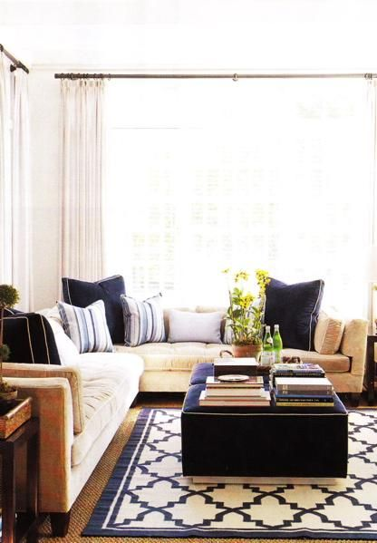 living rooms - mustard sectional sofa velvet blue throw pillows nailhead trim nail head trim velvet royal blue ottoman blue white Moroccan rug white drapes curtains wood accent tables end tables jute rug blue beige living room