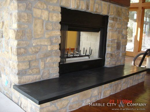 Fireplace with stone veneer and black granite hearth.