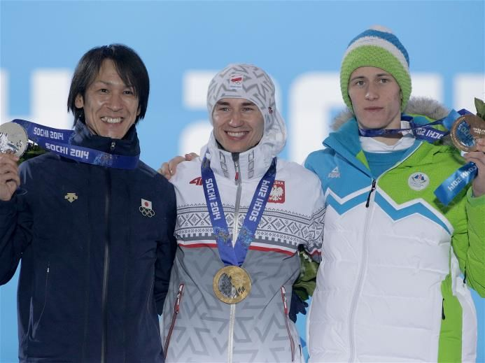 (L-R) Silver medalist Noriaki Kasai of Japan, gold medalist Kamil Stoch of Poland and bronze medalist Peter Prevc of Slovenia celebrate on the podium during the medal ceremony for the Men's Large Hill Individual on day 10 of the Sochi 2014 Winter Olympics at Medals Plaza