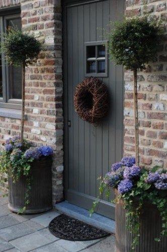 Wunderschöne Tür mit Weidenkranz und Blumentöpfen mit Stämmchen
