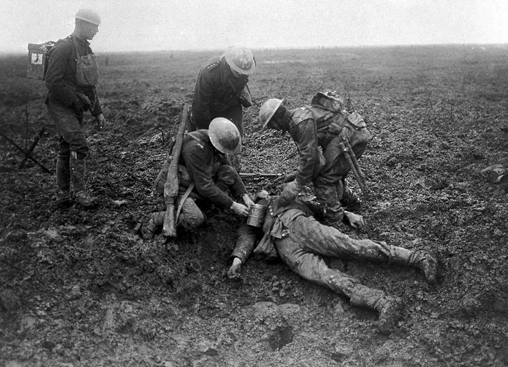 Canadian soldiers tend to a fallen German on the battlefield at the Battle of Vimy Ridge in 1917. (CC BY 2.0 Wellcome Library, London)