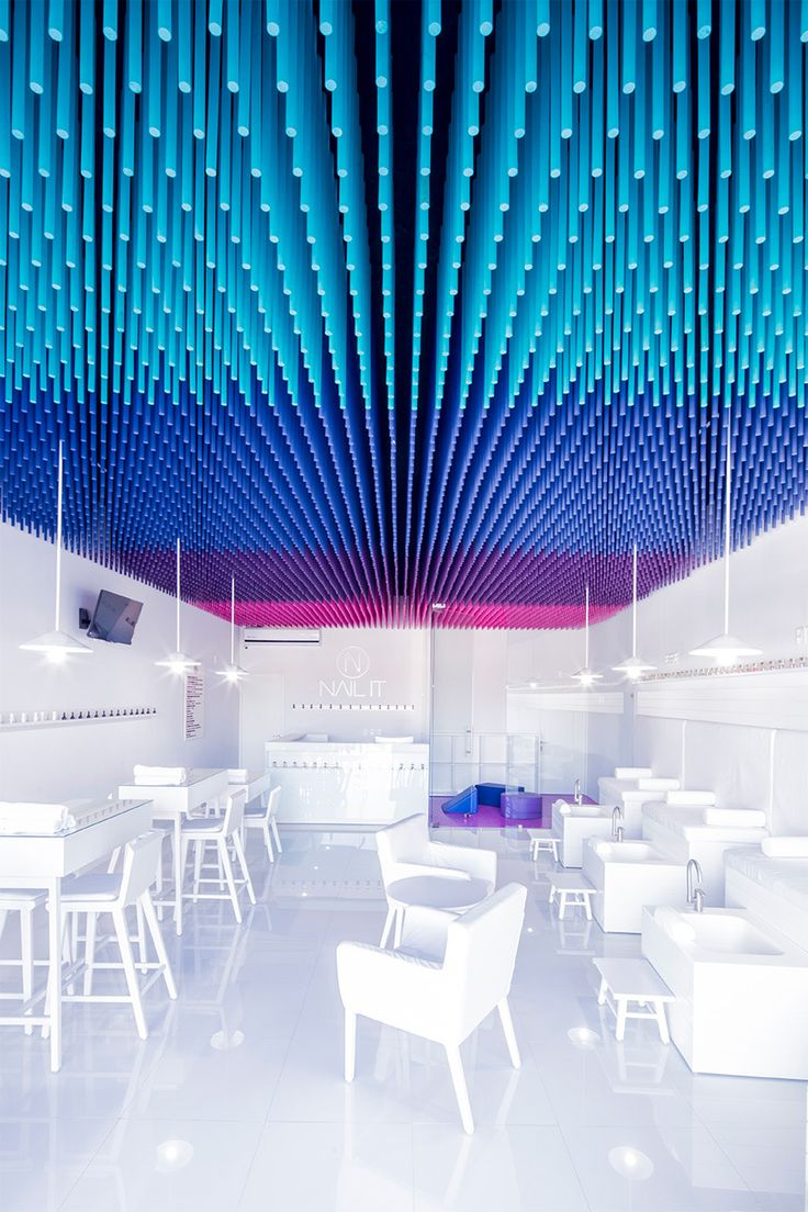 Salón de uñas en donde el color por medio de la instalación indica las diferentes áreas del espacio: Pedicure, manicure, recepción y ludoteca.
