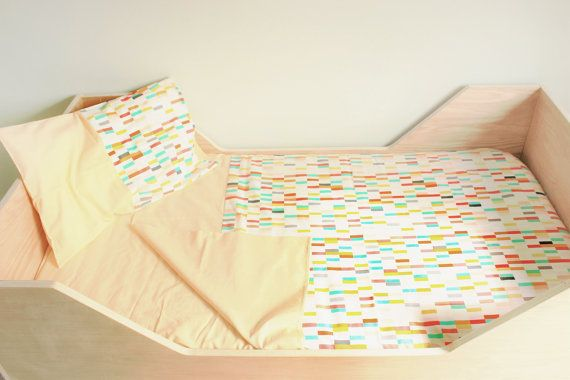Any child, even the ones that never want to go bed, will love snuggling under this lovely and soft colourful cover. The set includes 3 items: Crib/small toddler bed pillow cover (peach with an accent of rectangle fabric) Crib/small toddler bed fitted sheet (peach) Crib/small toddler bed duvet cover (peach on the back and mix of rectangle and peach fabrics on the front)  (Does not include duvet insert or pillow insert)  The pillow measures approx. 57cm x 37cm (approx. 22.5 x 14.5) and is made…