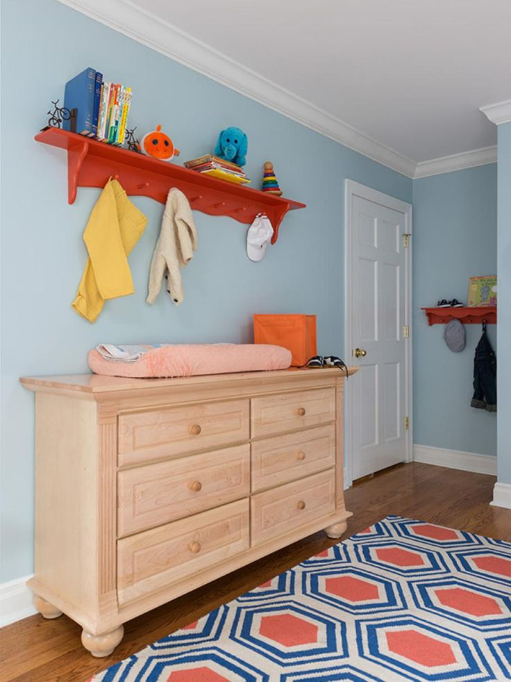 A mod orange-and-blue area rug adds style underfoot in this serene blue nursery. The light wood dresser provides plenty of storage and doubles as a changing table. Above, an orange coat rack is perfect for displaying books, toys and tiny clothing.
