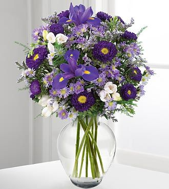 Purple iris are surrounded by lavender freesia, purple asters, and other soft accents in a glass vase.