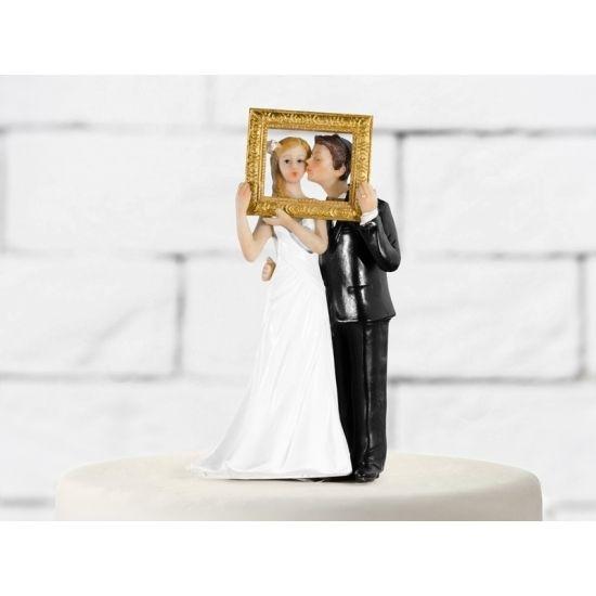 Taarttopper! Trouwfiguurtje met fotolijst. Leuk trouwfiguurtje van een bruidspaar die door een fotolijst heen kijken. Formaat: ongeveer 14,5 cm.