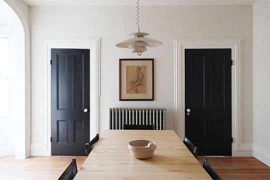 Black doors give this simple and minimalist dining area just the right amount of interest.