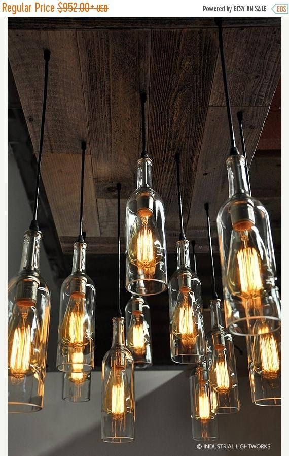 Eleven wine bottle pendant chandelier with a reclaimed wood base. One of a kind designed exclusively by Industrial Lightworks . A stunning chandelier design with 11 professionally cut and polished recycled wine bottles cascading from a reclaimed wood base. The pendant cord is