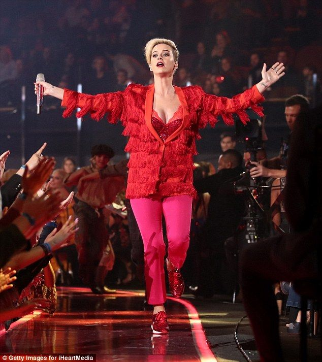 High energy: The 32-year-old pop star flaunted her cleavage in a red sequinned bodice paired with hot pink pants and a scarlet red tasseled jacket