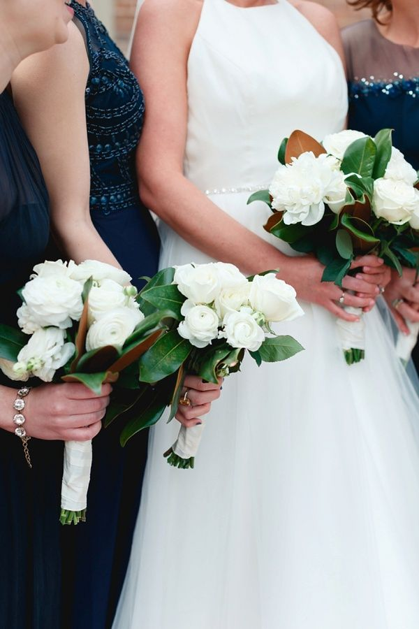 Southern wedding bouquets with magnolia leaves, roses, and ranunculus