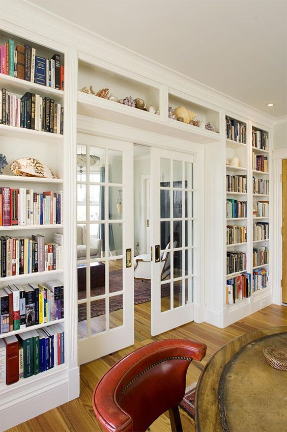 bookcases from the laundry area all around to the bedroom door...I like the glass pocket doors, although I think there is only room enough for one. also, like the shelves above the door. optimize space!