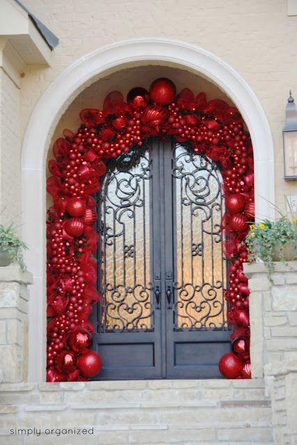 Una puerta decorada con esferas rojas que bonita Navidad!